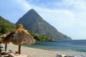 Sunbathing on a beach at Sugar Bay Soufriere, Saint Lucia next to the Pitons.